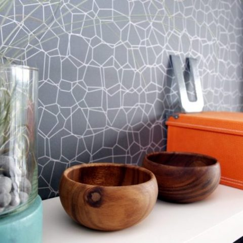 Orange and turquoise coloured accessories on floating shelf
