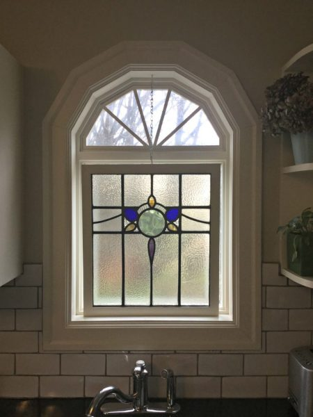 Stain glass panel in window above kitchen sink