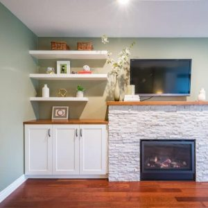 After fireplace renovation with ledgestone tile and custom cabinet
