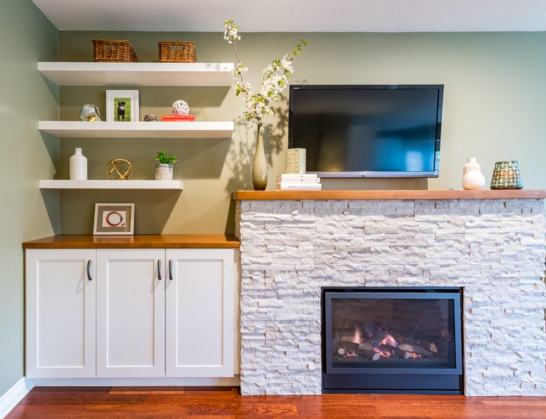 Custom cabinet and floating shelves with new fireplace surround