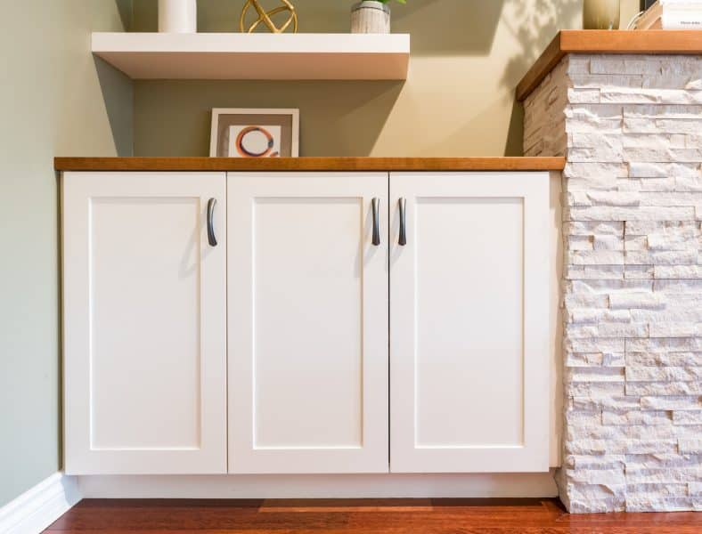 built-in white cabinet with wood top next to fireplace