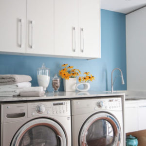 Modern laundry room painted turquoise walls with white cabinets
