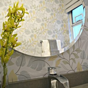 Decorated powder room with wallpaper, custom window valance, round mirror, quartz countertop