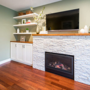 Renovated fireplace surround with builtin cabinet and floating shelves