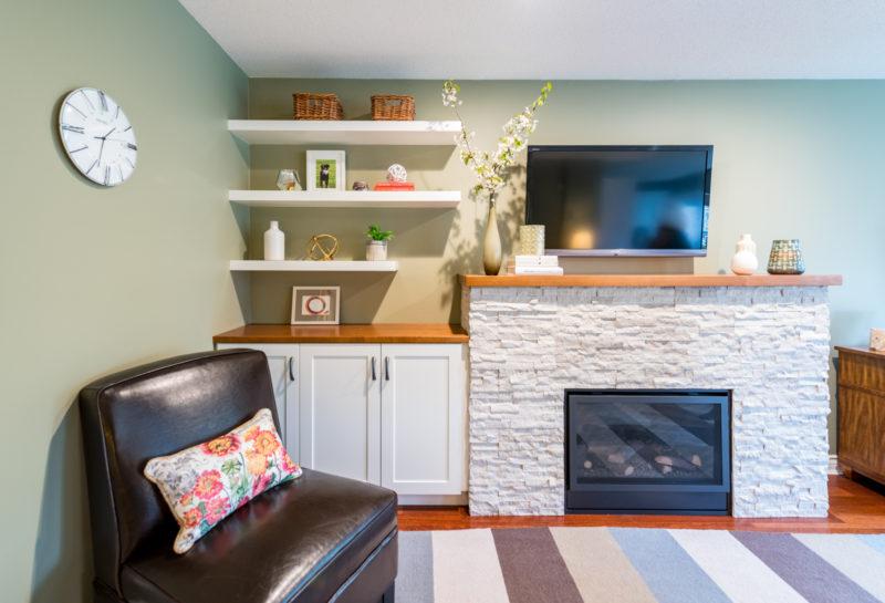 ledgestone tile on fireplace surround with custom cabinet and floating shelves