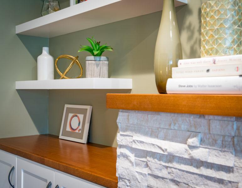 wood mantel on ledgestone tile fireplace surround with floating shelves
