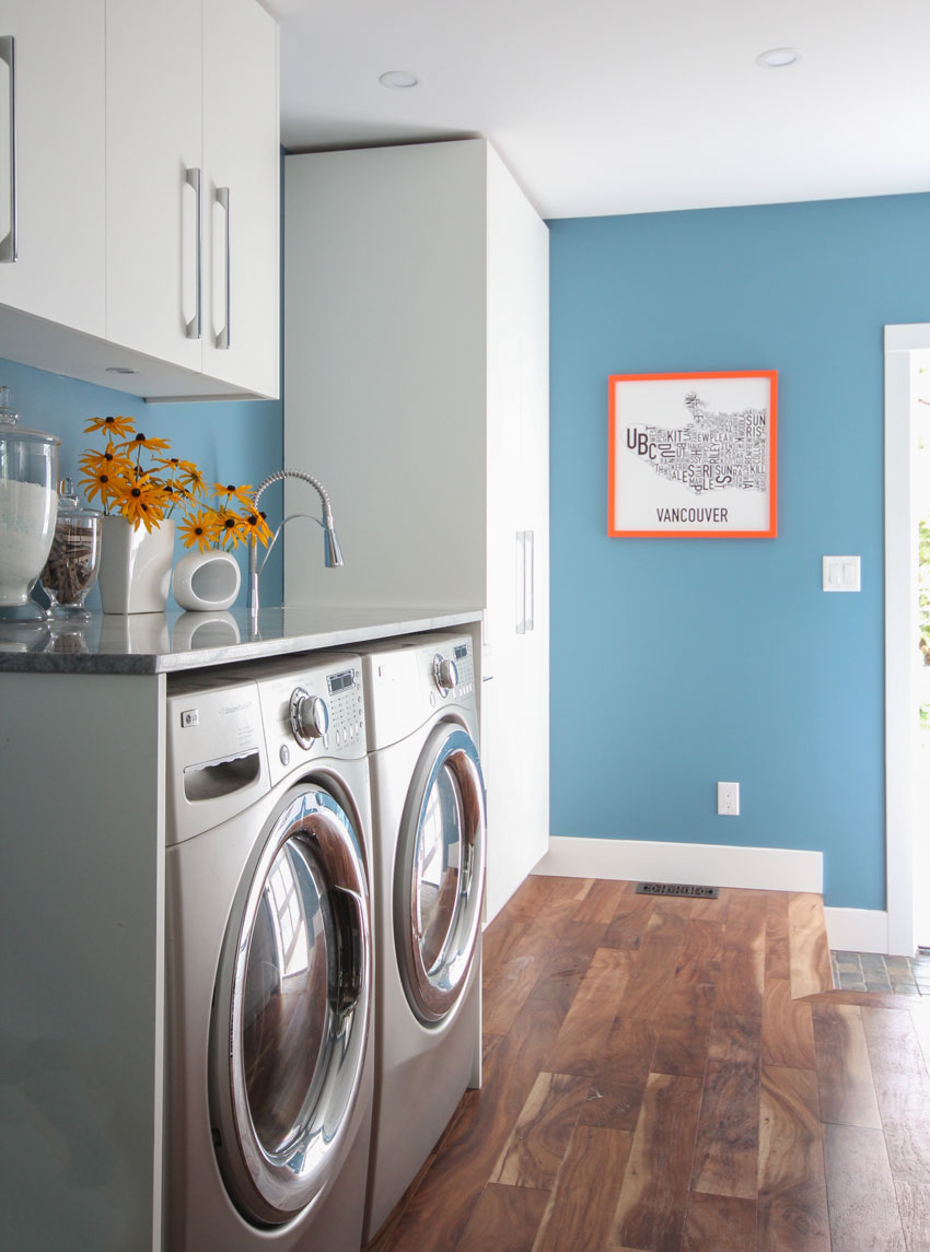 Laundry room with white cabinets, Acacia wood floors, Benjamin Moore Fiji paint colour on walls.
