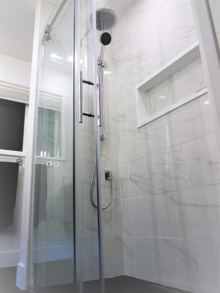 Walk-in-shower, glass sliding doors, custom built niche, rain shower, hand shower