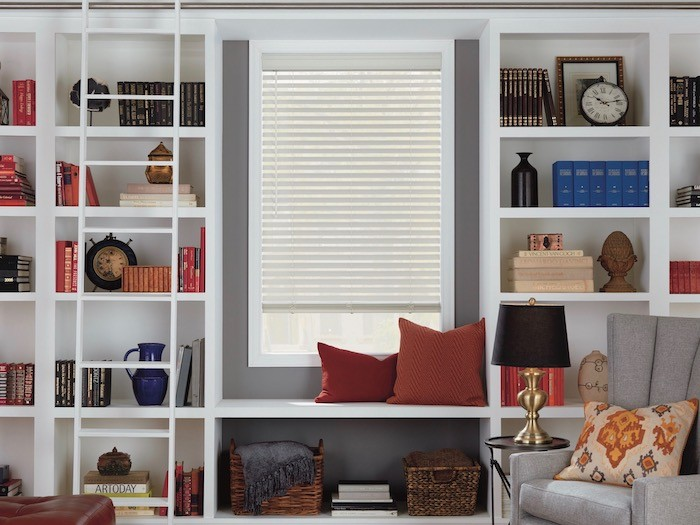 white built-in bookcases around a window